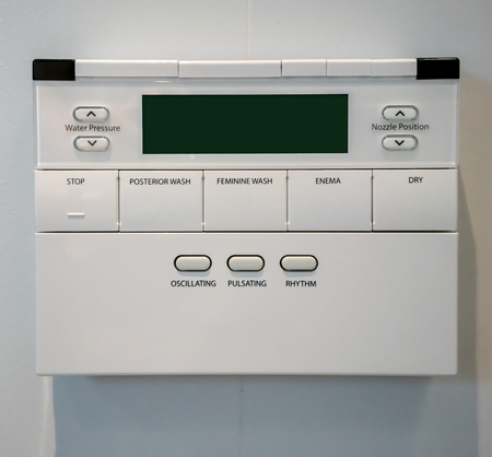 Control Panel of the toilet bowl on white wall. Hygienic and high technology of the toilet bowl, automatic modern flush toilet.
