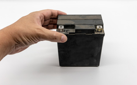 Hand holding the used motorcycle black battery isolated on white background. Stok Fotoğraf