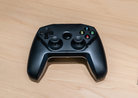 Wireless black joystick on wooden table background. Game controller.