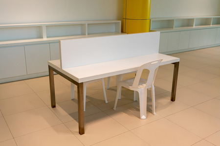 White empty desk with partition in modern office interior space. Interior detail design.