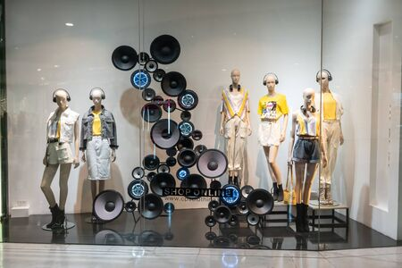 CPS shop at Siam Paragon, Bangkok, Thailand, Apr 25, 2019 : Fashionable brand window display. Standing models in different styles of colorful clothings. Editorial