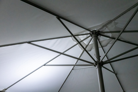 Metal Structure of an umbrella as abstract background. White umbrella with metal lines on a sunny day Stock fotó