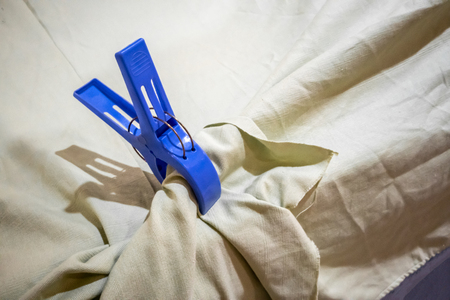Big blue plastic cloth pin clipped on white table cloth.