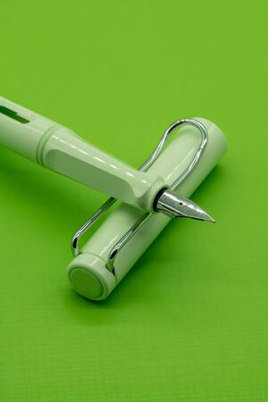 Light green calligraphic pen on green background with depth of field.