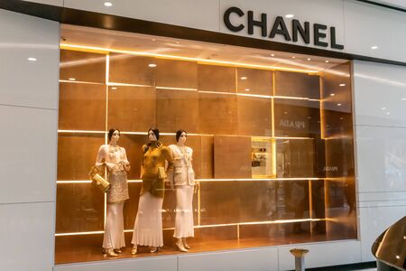 Chanel shop at Emquatier, Bangkok, Thailand, July 7, 2019 : Luxury and fashionable brand window display. New collection of Gold clothings and accessories showcase at flagship store. Perspective view.