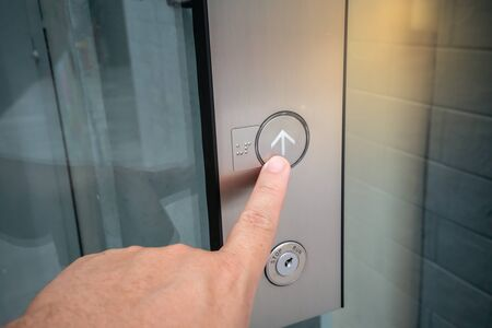 Male forefinger pressing on button up in front of the elevator in office building.