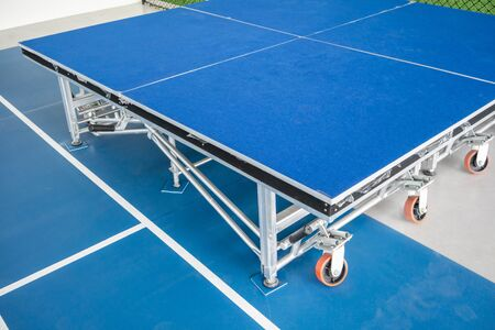 Foldable stage with blue floor with metal structure and orange wheels.