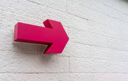 Pink arrow sign  hanging against white bricks wall for direction.