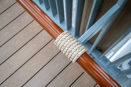 Light brown rope wrap around wooden bar along pedestrain way for decoration.
