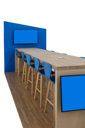 Wood desk and stools with LED TV hanging on modern blue partition isolated on white. Stok Fotoğraf