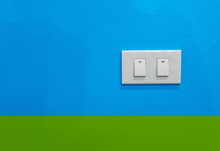 White double electric switches against blue and green background.