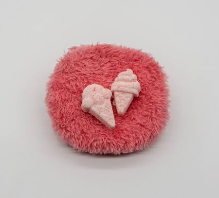 Cute Mini ice-cream bath bomb on red fluffy carpet like isolated on white background for valentines vibe.