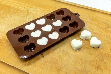 DIY Cute Mini heart bath bomb from silicone chocolate mold on wooden tray isolate for background. Valentines gift idea.