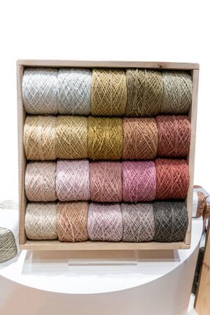 Colorful yarn on spool, yarn on tube, cotton, wool, linen thread on wooden display shelf.