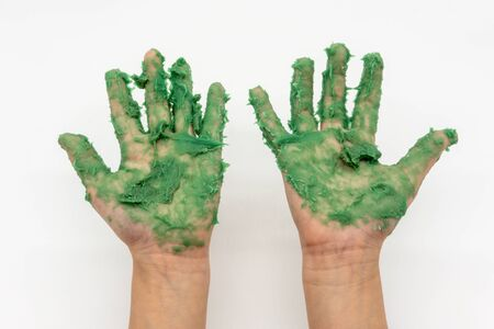 kid hand with green mudy play dough isolated on white background. 版權商用圖片