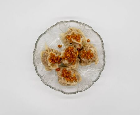 Chinese traditional delicacies, fresh meat wontons on clear plate isolated on white background.