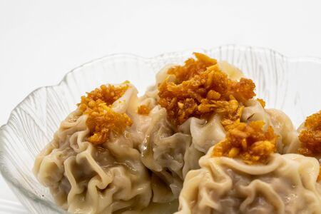 Close up on fried garlic on top of wontons in clear plate isolated on white background. 版權商用圖片