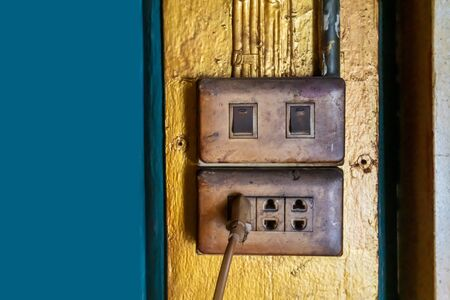 Old and dirty electric switches and plugs against old gold background. 版權商用圖片