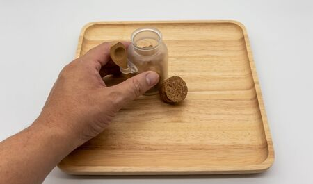 Hand holding mini bottle of Rock sugar with cork lid on wooden cutting board and empty space for add on objects isolated on white background. 版權商用圖片