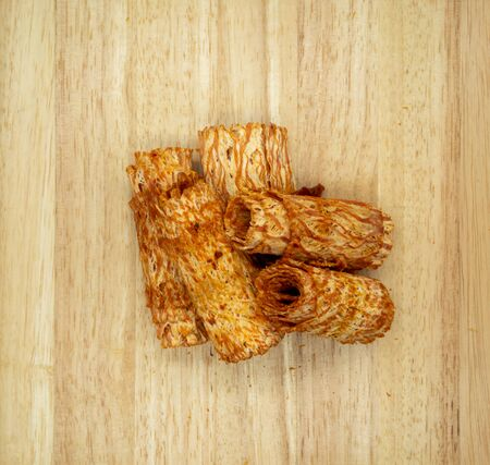 Rolls of Spicy dried squid on wooden cutting board isolated on white background. Fine chili seasoning seafood snacks.