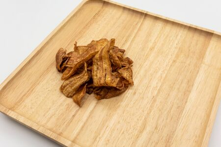 Honey coated crispy baked banana slices on wooden cutting board isolated on white background. Thai style homemade healthy sweet snacks. 版權商用圖片