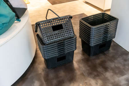 Stack of black plastic shopping baskets on ground floor ready for customer to pick up.