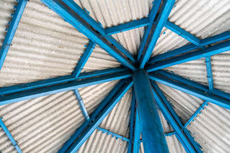 Blue metal roof structure with grey roof tile on top.