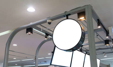 Blank round signboard hanging from kiosk display metal structure. Interior design detail.