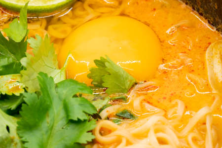 Closeup on an egg in pork spicy 'Tom Yum' with instant noodle soup in hot pot. Thai famous food. Stock fotó