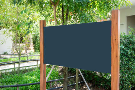 Black board mockup with wood poles structure against nature background. Stock fotó