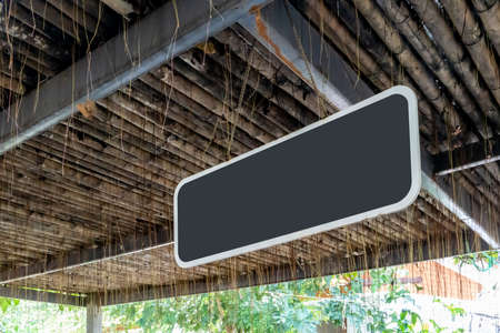 Black wooden chalk boards hanging from the wood roof. Selective focus for retro background. Signage Mockup