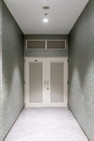 White swing doors with air ventilator on top against gray wall background.