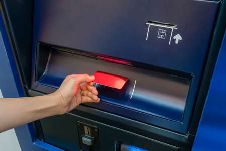 Hand of Asian woman inserting card into dark blue payment machine for scanning.
