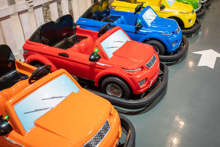 Colorful electric toy cars for kid on gray floor background.