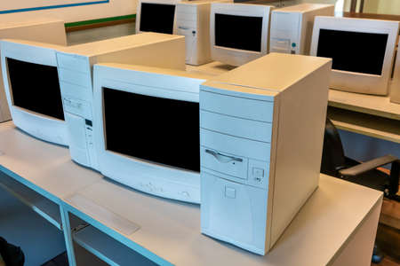 old CRT computer monitors and towers in classroom or office.