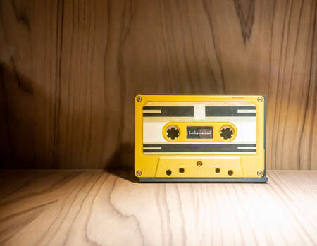 close up of old and dirty vintage audio tape cassette in yellow plastic case on wooden background.