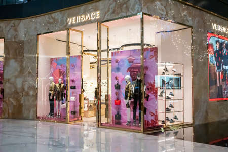 Versace shop display at Icon Siam, Bangkok, Thailand, Nov 28, 2020 : Luxury fashionable clothing and shoes visual merchandising and window shopping in Gold Christmas greeting.