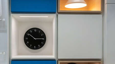 Black clock hanging on white cabinet wall for decoration. Interior design detail