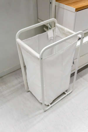 White fabric basket with white metal frame in laundry room. Stock fotó