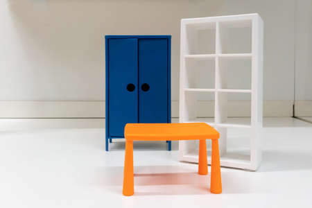 Miniature toy orange plastic table, white shelf and blue cabinet on white room  background. Stock fotó