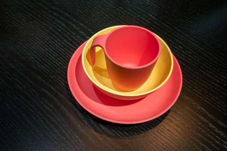red and yellow plastic mug cup and dished on black wooden table