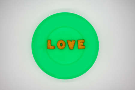 Letter biscuit in order for LOVE on green plastic plate or dish isolated on white background. Valentine concept