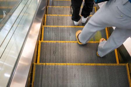 Walking feet wearing on escalator. Transportation and circulation concept.