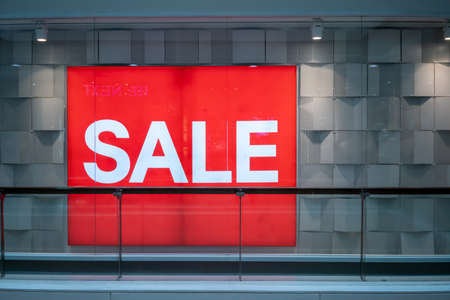 Red sale sign on clear glass store window against white wall background.