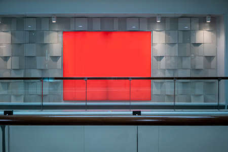 Red blank sign on clear glass store window against white wall background.
