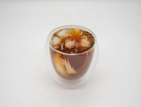 Iced coconut coffee in double walls glass isolated on white background. Selective focus.