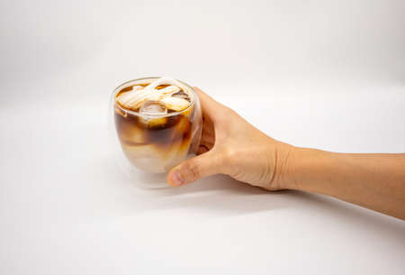 Hand holding iced coconut coffee in double walls glass isolated on white background. Selective focus.
