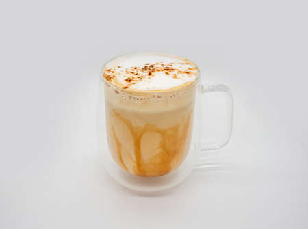 Hot coffee with milky foam sprinkle with cocoa power for decoration in double wall glass isolated on white background.