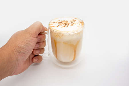 Hand holding hot coffee with milky foam sprinkle with cocoa power for decoration in double wall glass isolated on white background.