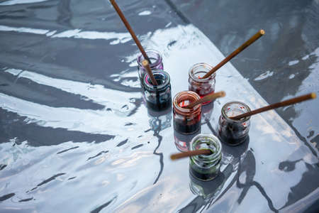 ink colors in clear glass bottles with brushes on dark table with clear plastic cover.
